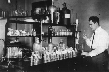 Paul Galtsoff standing at table full of glass instruments at his lab in Woods Hole, 1924