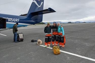 Group photo of survey team standing in front of a NOAA Twin Otter aircraft on the tarmac.