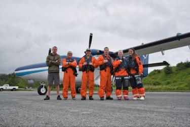 Photo of team standing in orange flight suits on the tarmac in front of NOAA Twin Otter aircraft.