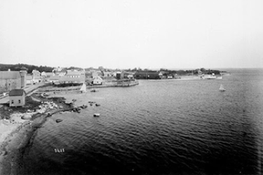 Black and white photo, date unknown, of the waterfront area along what is now Water Street, taken from the roof of the fisheries residence looking toward the steamship authority facilities and Juniper Point on the far right.