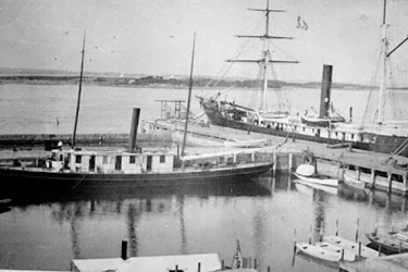 Steamer vessels Phalarope and Albatross at the new Woods Hole Lab dock in Woods Hole in the 1880s. Phalarope is tied up at the wharf inside the boat basin, with many smaller boats tied up nearby. Albatross is outside the refuge, alongside the wooden wharf with the drawbridge.