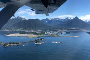 Aerial photo of Sitka and with small islands and airport in the foreground and mountains in the background.