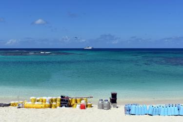 A photo taken from a beach on Laysan Island field camp supplies staged before the pick-up by NOAA ship (seen on the horizon).