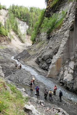 An image from above of nine people at the former site of the lower Eklutna dam.
