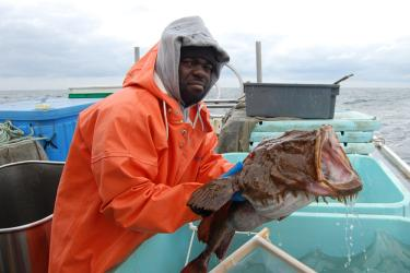 Man holding a tagged monkfish.