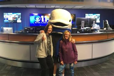 Person in a Cook Inlet Beluga whale costume poses with Sue Goodglick and another woman on KTVA in Alaska.