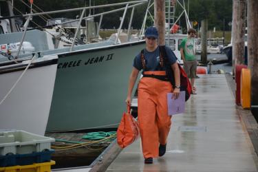 Observer in orange rain gear, with supplies walking on dock.