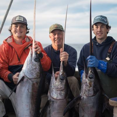 Bill Bright and two men pose with swordfish.