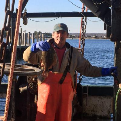 Rodman Sykes holds up a flounder aboard his fishing vessel.