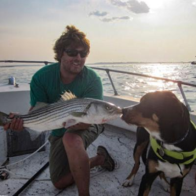 Ethan Wood nose boops his dog with a striped bass while on a boat.