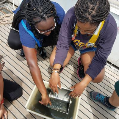Two PEP students view a sediment sample collected at sea during their research cruise.