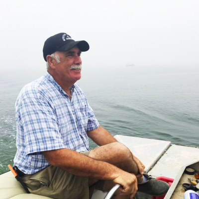 Jim Markow sits on a boat, preparing to work on the water on a foggy day.