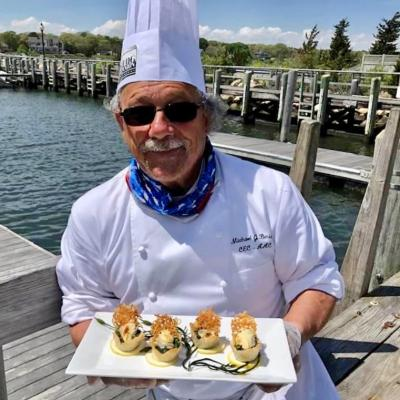 Mick Beriau holds a plate of butter-poached oyster tartlets dockside at Woods Hole Sea Grant's shucked oyster cook-off at-home event in June 2020.