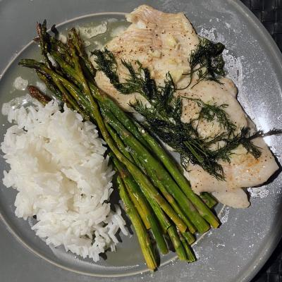 Tautog fillets served with dill, rice, and asparagus on a plate.