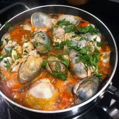Clams in red sauce boiling in a pan on a stove.