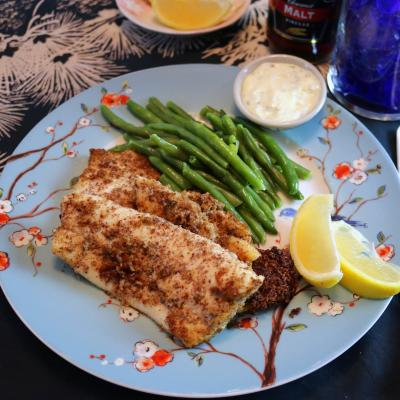 Flounder fillets served with green beans on a plate.