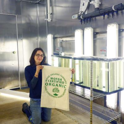 Sarah Redmond holds a certified organic certification flag in a seaweed farm culture room.