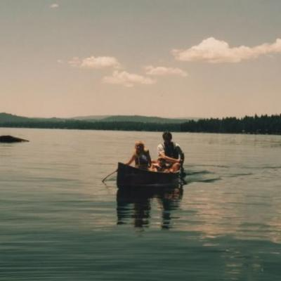 father and two girls canoeing in lake