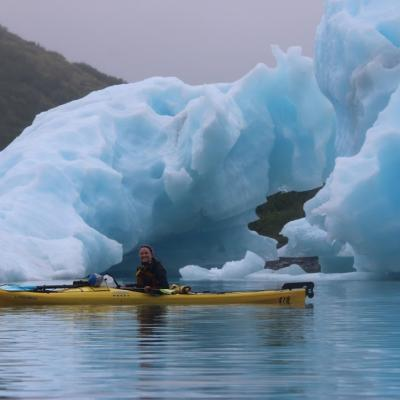 Smiling woman kayaking near glaciers
