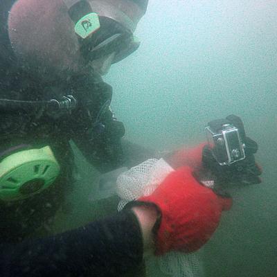 NOAA Diver Mark Dixon adjusts a GoPro camera underwater.
