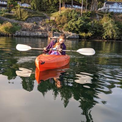 Smiling woman kayaking with her baby near Fox Island, Washington