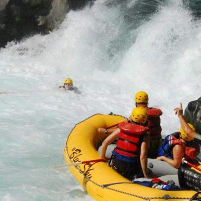 woman swimming near a raft full of people