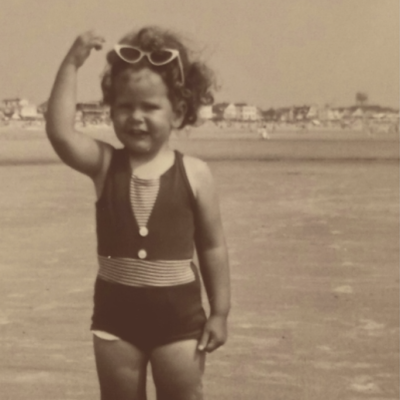 black and white photo of a very young girl in a bathing suit on the shore