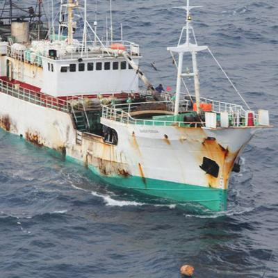 A large IUU ship surges forward through the water.