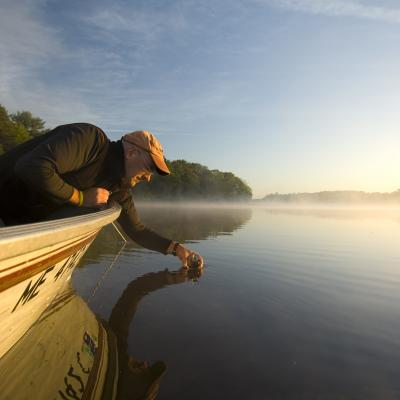 Penobscot Nation Water Resources Program Manager Dan Kusnierz leans over the side of a small boat, holding a sample bottle