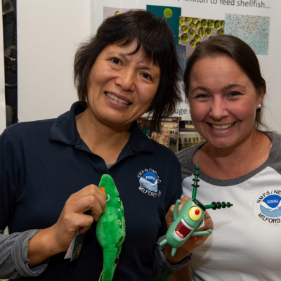 Research ecologist Judy LI and biological laboratory technician Melissa Krisak stand in front of a poster on phytoplankton ecology during Milford Laboratory Open House in 2018.