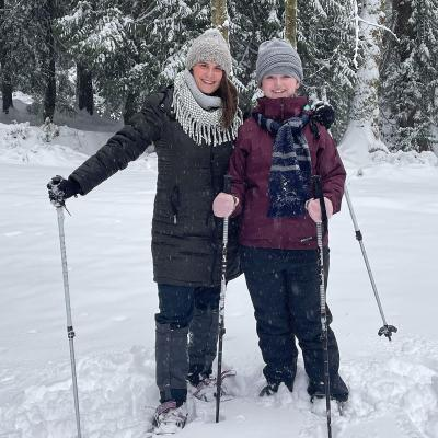 Two people with snow shoes and poles smiling for the camera