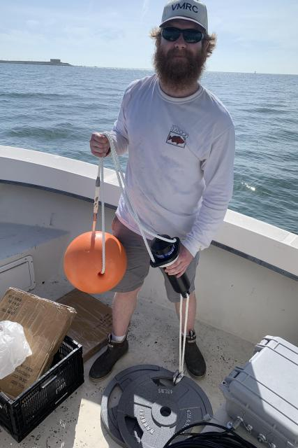 A man stands on a small boat while holding scientific equipment.