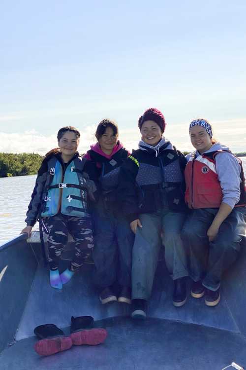 Photo of four women wearing life jackets sitting in the prow of a boat on the Yukon River.