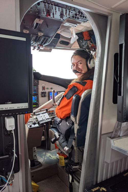 Photo of Burlyn wearing orange flight suit and sitting in the NOAA Twin Otter cockpit during flight, taken from rear cabin.