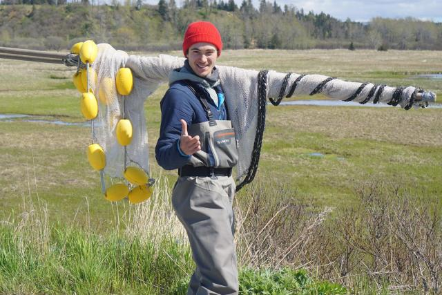 A scientist carrying a salmon net for research