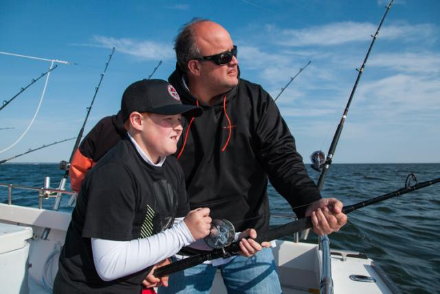 An adult helps a child fish from a charter boat in the Chesapeake Bay.