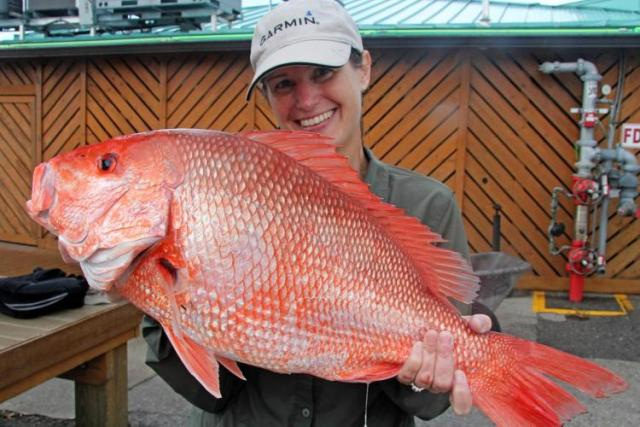 Woman with Red Snapper fish.