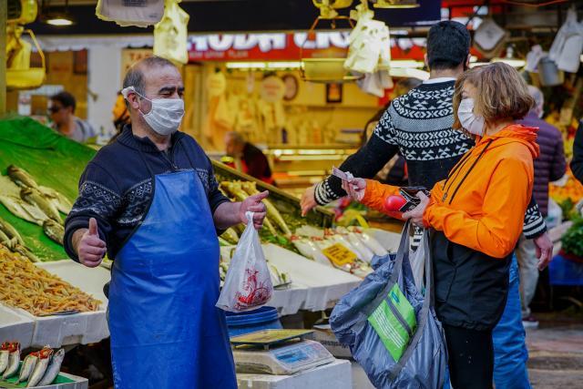 Photo of people at a fish market wearing masks due to Coronavirus.