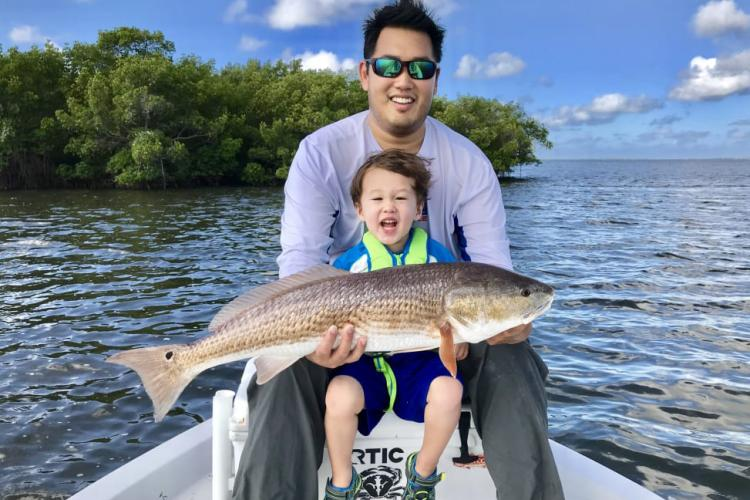 Father and daughter fishing, holding a caught redfish.