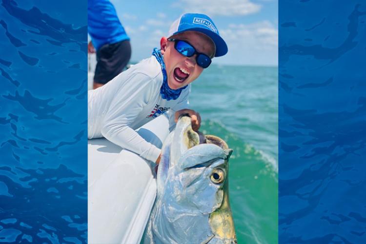 Boy fishing, holding tarpon