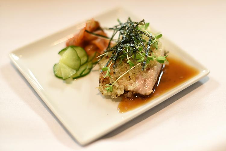 Tuna fish (ahi) on rice served with soy sauce on a plate.