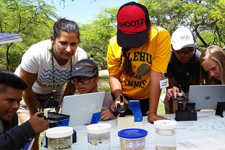 Students and marine biologists helping students study plankton at an outreach booth.