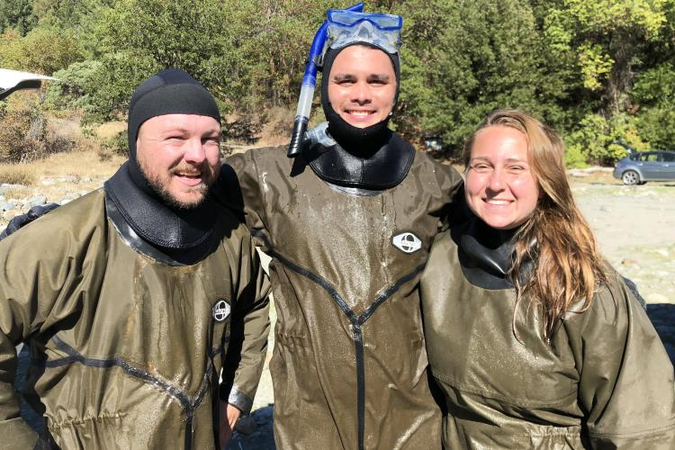 Three veterans corps participants pose in snorkeling gear after monitoring a stream restoration project.