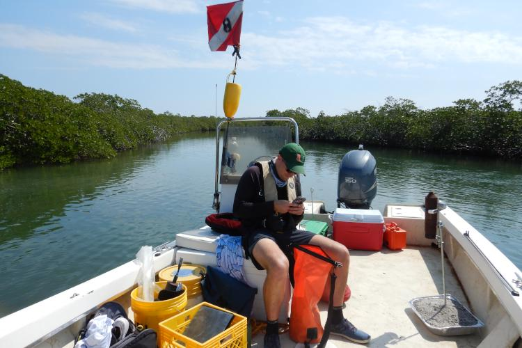 Graduate student and SRC Coordinator Mitchell Rider rechecking geographic coordinates before redeploying the acoustic receiver on the deck before him.