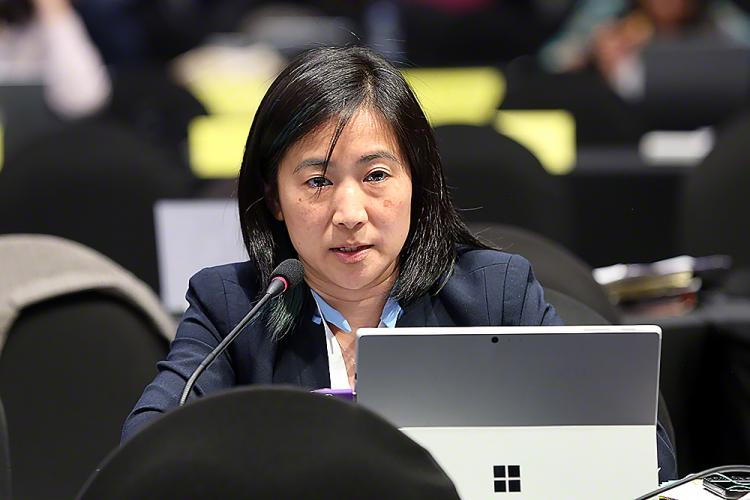 Kristen Koyama in a blue shirt and black blazer sits behind a microphone and computer
