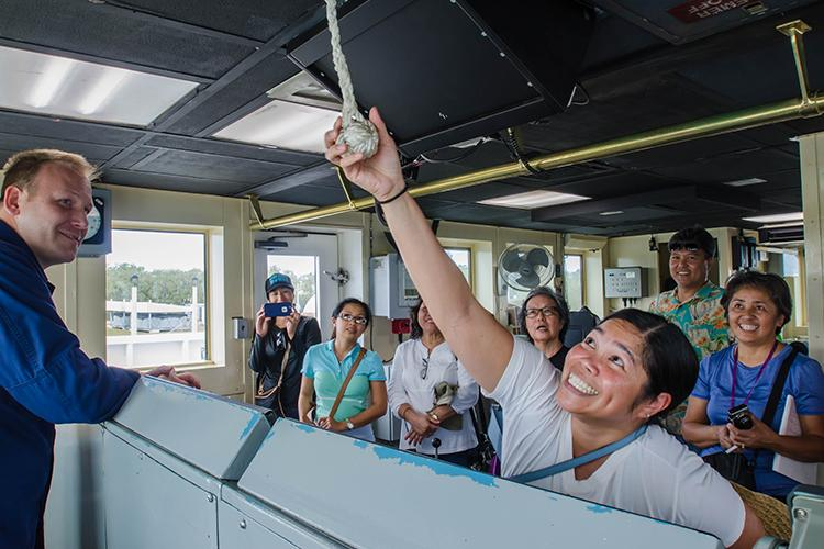 Group of students and educators exploring the inside of a NOAA Ship.