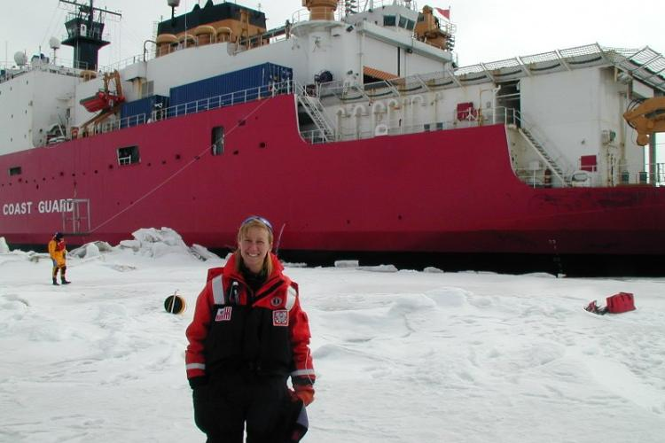 Photo Ingrid Spies standing on an ice sheet in front of an icebreaking vessel.