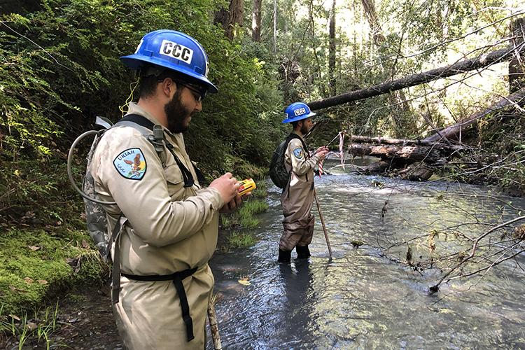 Two people in blue CCC hard hats stand knee-deep in a river