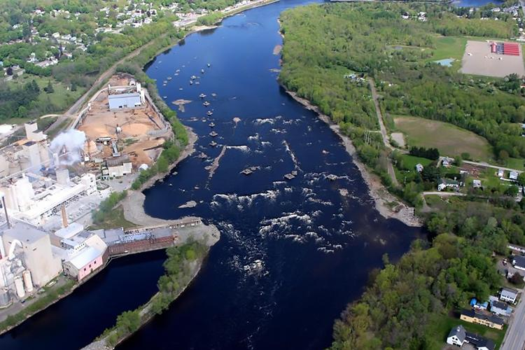 Aerial photo of a river flowing next to an industrial plant