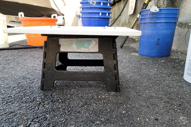 Flat-topped plastic stool with sturdy legs on the deck of a small commercial fishing vessel